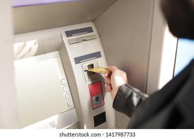 Man inserting credit card into cash machine outdoors, closeup
