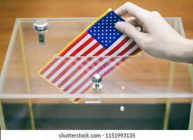 Man inserting Flag of United States of America into ballot box, voting and elections in United States of America.