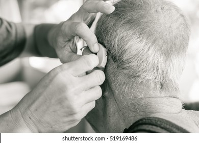 Man inserting hearing aid in senior's ear. black and white tone filter.