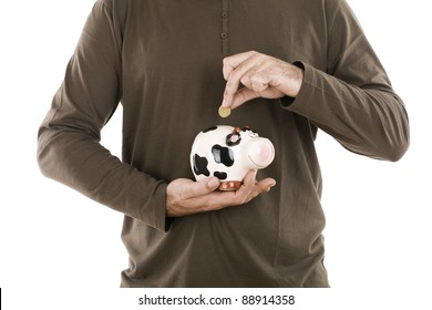 man inserting money in a piggy bank is a cow