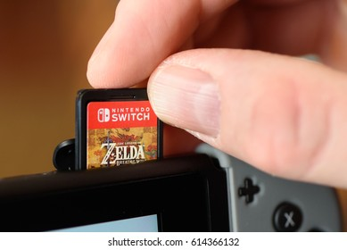 A man inserting a Zelda Breath of the Wild video game cartridge into a Nintendo Switch console. Fogelsville, Pennsylvania, USA on March 19, 2017.