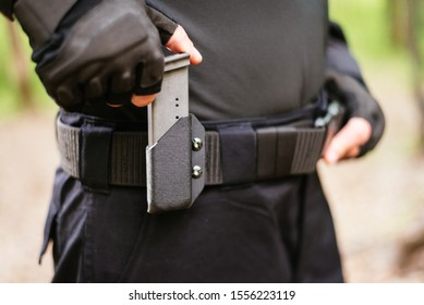 a man inserts a magazine from his pistol into the holster