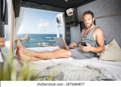 Mann im Wohnmobil mit Laptop und Smartphone