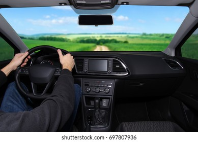 The man inside the car is driving along the road