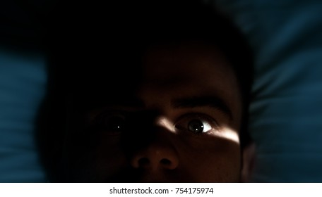 man with insomnia, light shines in the eye