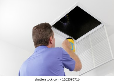 Man Inspecting an Air Duct with a Flashlight. Older male with a yellow flashlight examining HVAC ducts in a large square vent. Male technician looking over the air ducts inside a home air intake vent.