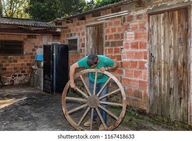 A man inspects an old wooden wheel.