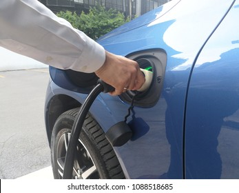 the man install the power cable supply plug for charging the EV Car or Electric car at charging station