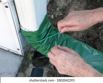 A man is installing an automatic recoiling extender over the downspout that rolls out when it's raining and up when it's dry to prevent foundation damage from water.