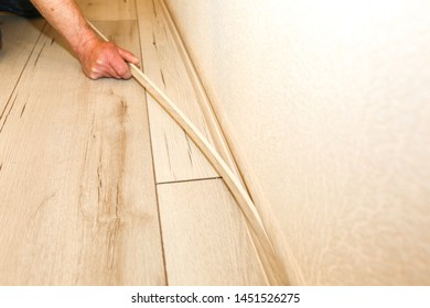 Man is installing the baseboard. Repair works indoors. Renovation in the flat.