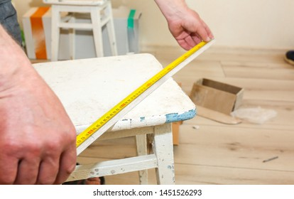 Man is installing the baseboard. Repair works indoors. Renovation in the flat.  Tape measure in hands.