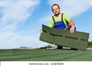 Man installing bitumen roof shingles - holding a few pieces