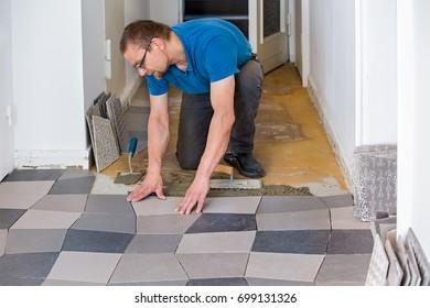 Man installing ceramic floor tiles in new house