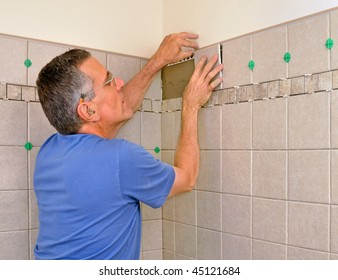 Man installing ceramic tiles on bathroom wall in shower area