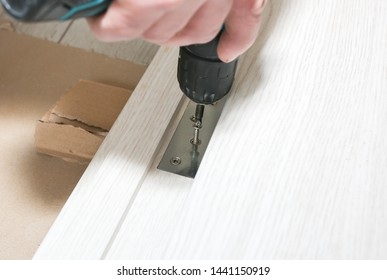 Man is installing the doors. Carpenter is making holes with the drill in hinges. Repair works. Maintenance in the apartment.
