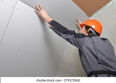 Mann, der Trockenmauerpaneele baumelt