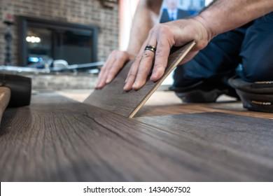 man installing engineered laminate wood floring indoor