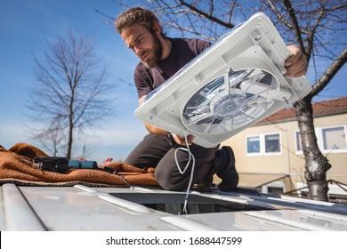 Mann, der einen Ventilator auf dem Dach seines Wohnwagens installiert