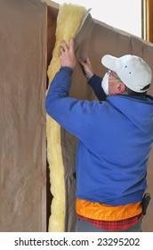 Man installing fiberglass insulation to wall cavity