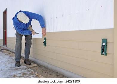 Man installing fibrous cement siding using siding gauges