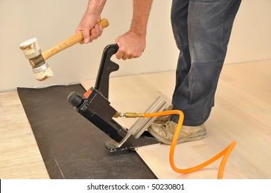Man installing hardwood flooring with a pneumatic nailer