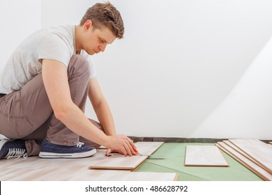 Man installing light laminate flooring in a room