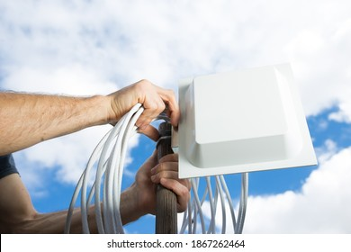 Man installing MIMO 4G antenna to improve cellular coverage on deep village. - Shutterstock ID 1867262464