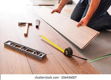 Man installing new laminated wooden floor