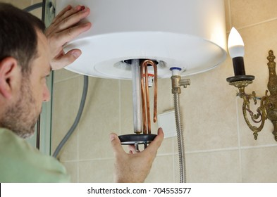 Man installing a new water heater in a boiler