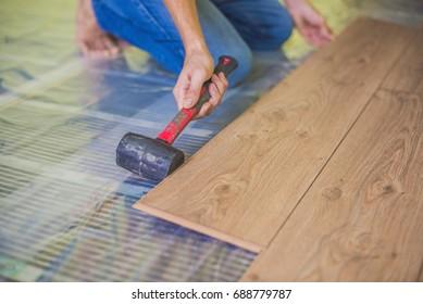 Man installing new wooden laminate flooring on a warm film floor. infrared floor heating system under laminate floor