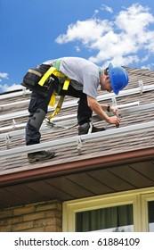 Man installing rails for solar panels on residential house roof