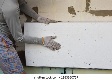 Man installing rigid styrofoam insulation board for energy saving on exterior wall of building. Rigid extruded polystyrene insulation for house improvement.