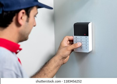 Man installing security alarm system