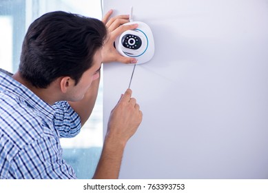 Man installing surveillance CCTV cameras at home
