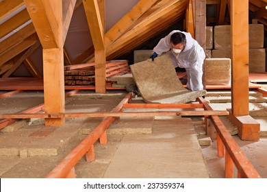 Man installing thermal insulation layer under the roof - using mineral wool panels