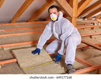 Man installing thermal insulation panels between wooden scaffolding
