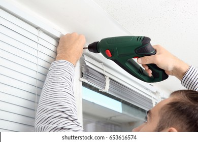 Man installing window shades at home