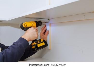Man installing wooden shelves on brackets wall installing a shelf