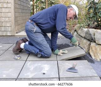 Man installs flagstone pavers on patio