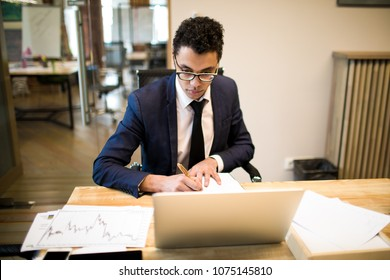 Man intelligent economist writing notary in textbook during work on portable laptop computer. Male creating new business plan sitting at table with netbook and paper documents with financial charts