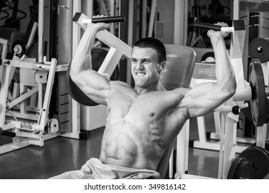 Man intensely performs exercises on the simulator in the gym.