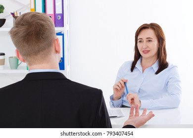Man is interviewed at office background. Businesswoman and businessman have meeting and conversation. Copy space and mock up. Selective focus