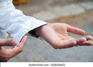 A man investigating his hands and sleeves with yellow stains Before dressing up for work