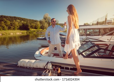 Man inviting a woman to his motorboat sitting in the river port, taking her hand
