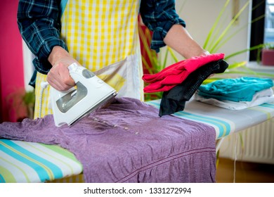 man with iron on ironing board with clothers in living room