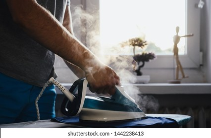 Man is ironing clothes. The concept of caring for the home, helping men in household chores. The man uses an iron to iron the child's clothes.