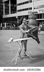 Man ironing his suit in the city in a business area in front of office buildings