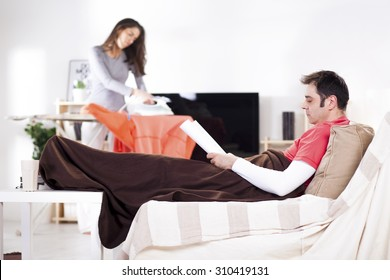 Man ironing and relaxing in the living room, woman is ironing in