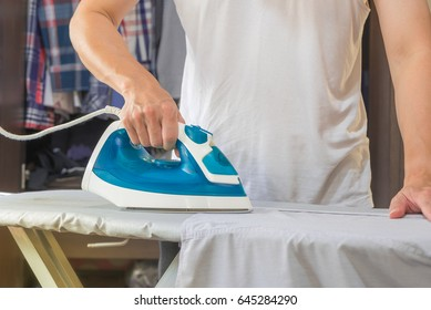 Man ironing shirt on ironing board with steaming blue iron.