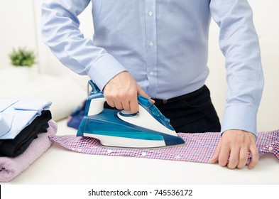 Man ironing shirt on ironing board. Steaming blue iron. Clothes ironing board household concept